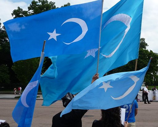 Uyghur activists march with the flag of East Turkestan.