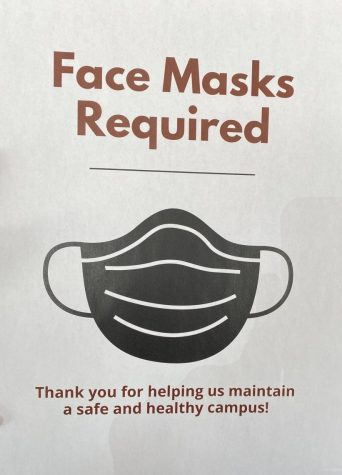 Signs directing mask requirements greet entrants to campus.